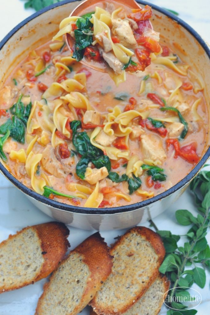Creamy Tuscan chicken noodle soup is the perfect cold weather meal! Loaded with chicken, noodles, sun dried tomatoes and spinach in a creamy garlic tomato broth! via firsthomelovelife.com
